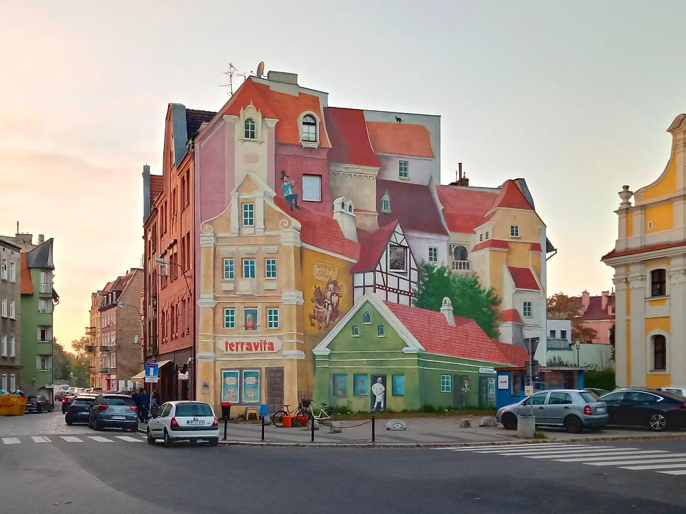 Zielona Symfonia Śródka Poznań mural Opowieść śródecka z trębaczem na dachu i kotem w tle