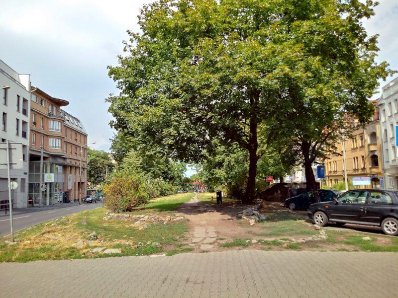 Ulica Kościelna: po obu stronach kamienice, pośrodku zielony plac