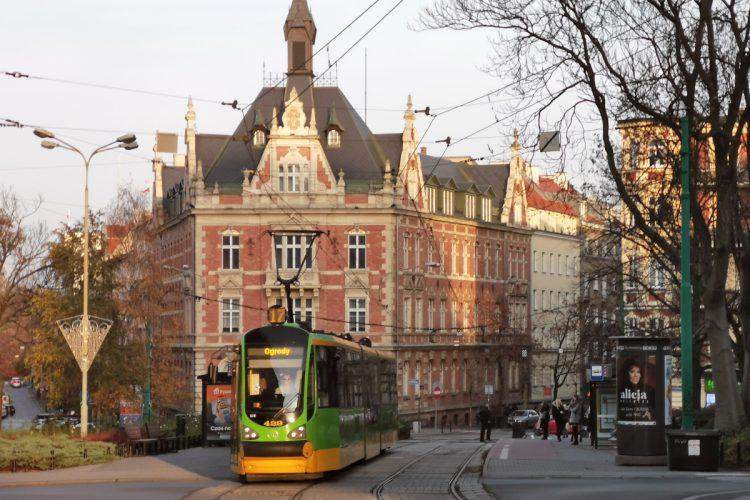 Plac Cyryla Ratajskiego: z przystanku odjeżdża tramwaj MPK Poznań, pogoda typowo jesienna