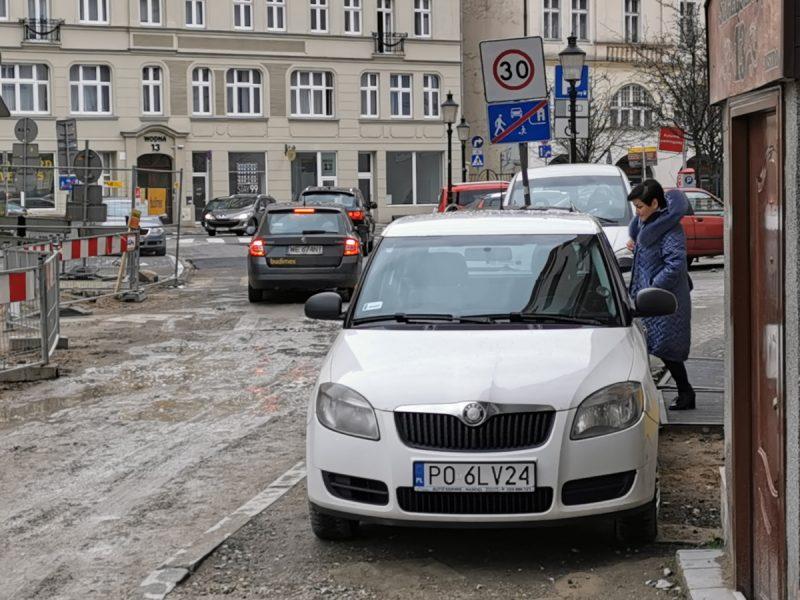Codzienność pieszych na remontowanym placu Kolegiackim - fatalne parkowanie kierowców. Piesza musi iść po błocie, gdyż nie zmieści się między murem a autem...