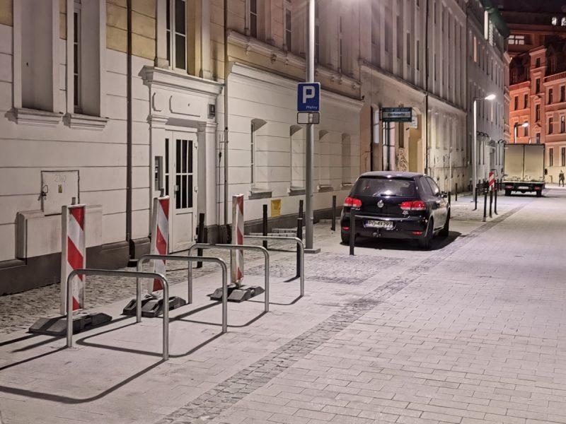 Ulica Garncarska: stoją stojaki rowerowe, pojawiają się znaki drogowe
