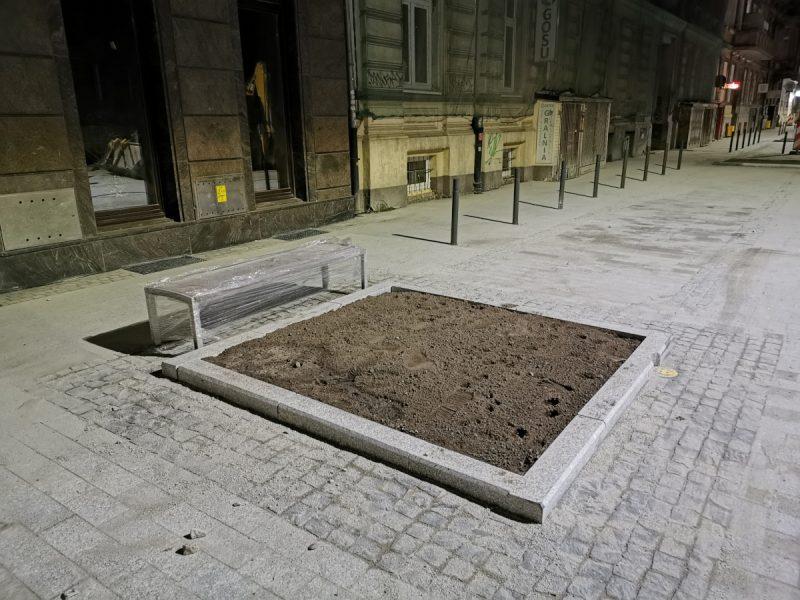 """Budowlańcy montują małą architekturę - tutaj widzimy ławkę. Natomiast już niedługo w """"dziurach"""" z ziemią pojawią się drzewa"""