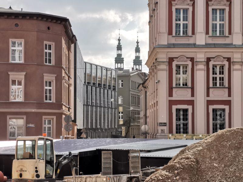 Zbliżenie na zadaszenie wykopu, w tle ulica Wszystkich Świętych. Rewitalizacja centrum Poznania