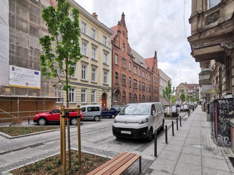 Projekt Centrum Poznań. Chodnik po południowej stronie. Na pierwszym planie ławki (większość nie posiada oparcia)