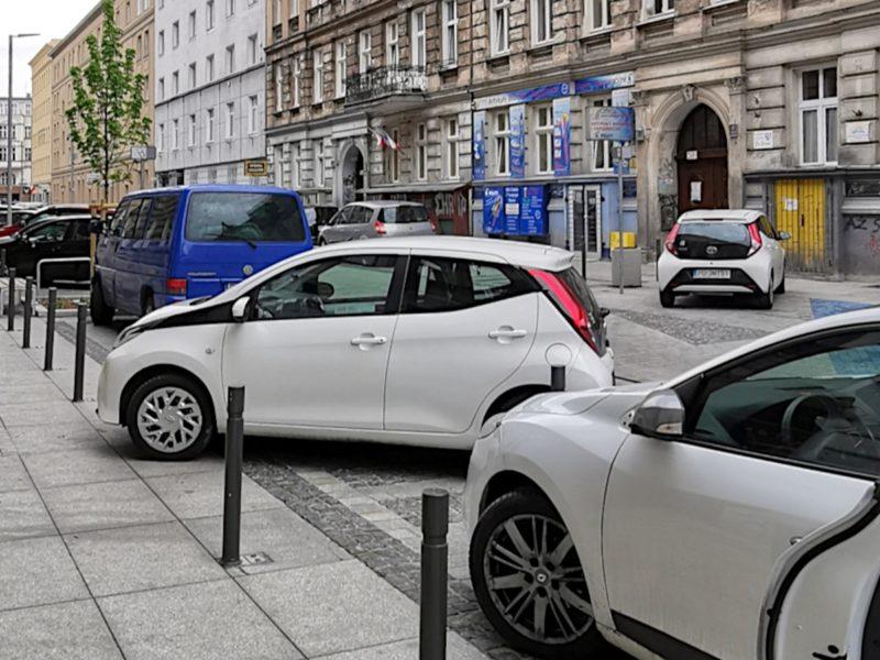 Dwa białe samochody parkują nielegalnie. Choć zamontowano sporo słupków, to kilka miejsc pozostaje niezabezpieczonych