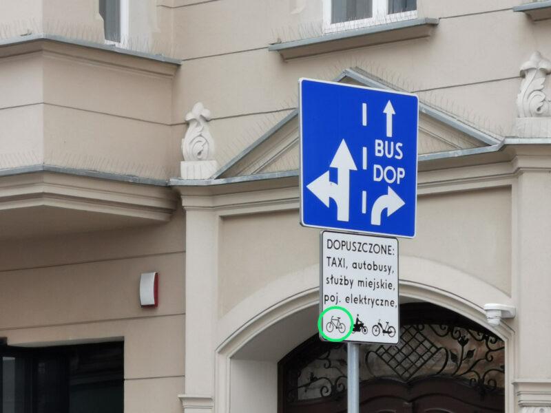 Oznakowanie buspasa na ulicy Garbary. Zielonym okręgiem zaznaczono symbol potwierdzający możliwość jazdy rowerem po buspasie