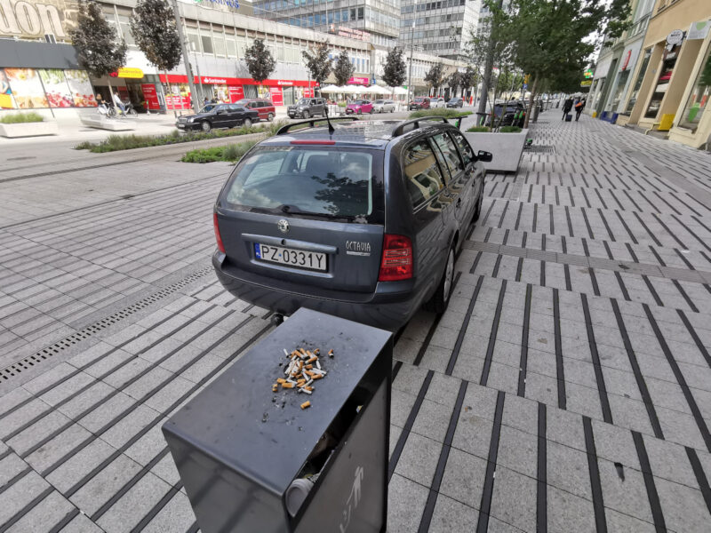 Popielniczka (ktoś ją w ogóle czyści), a w tle nielegalnie parkujący samochód zastawiający przejście przez jezdnię