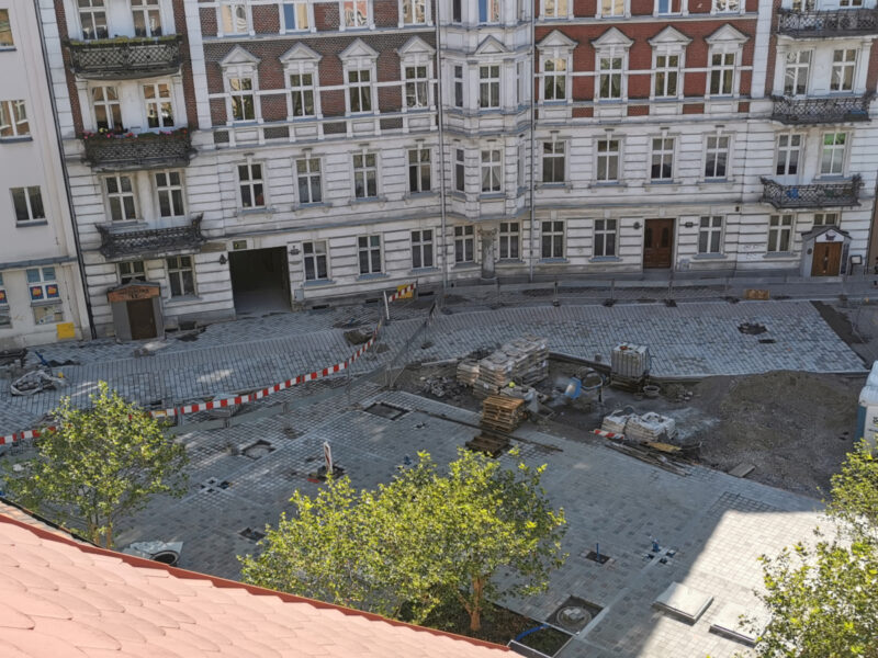 Wschodnia część placu Kolegiackiego, na której przybywa kostki