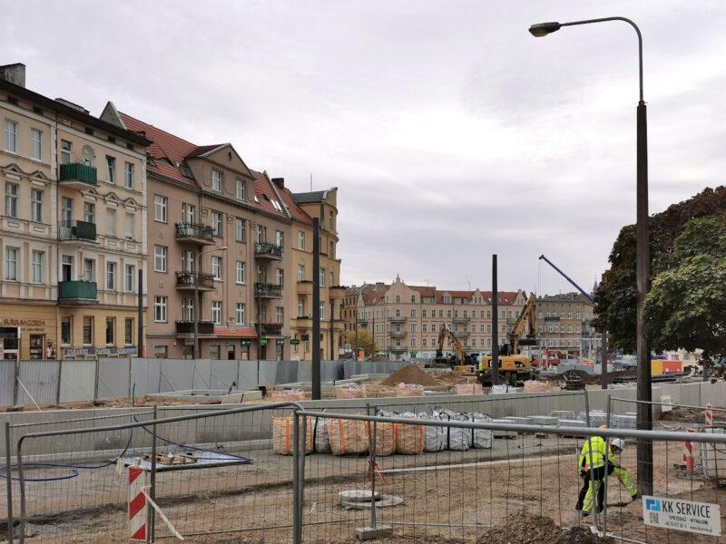 Na skwerze Kazimierza Nowaka stoją pierwsze słupy pod latarnie. Widzimy też pierwsze warstwy podbudowy pod miejsca postojowe (tuż przy murze)
