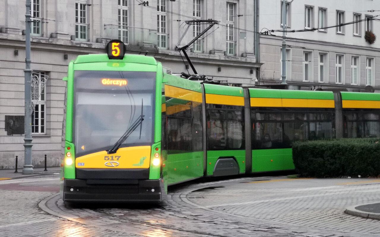 """Tramwaj Solaris Tramino odjeżdża z przystanku """"Marcinkowskiego"""" i wjeżdża na plac Wolności (pojazd MPK Poznań), pogoda pochmurna"""