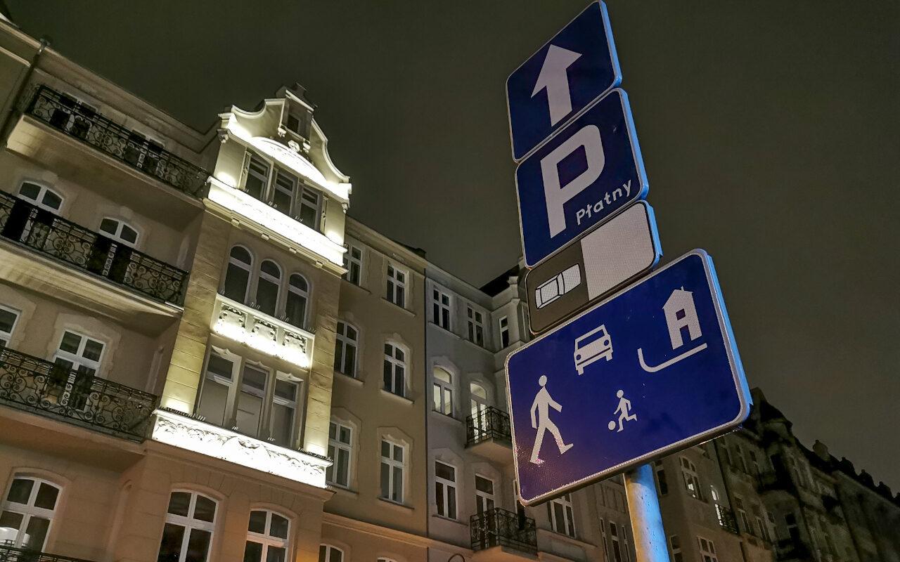 Poznań nocą: ulica Wielka. Na słupku wisi kilka znaków, w tym oznajmiający wjazd do strefy zamieszkania