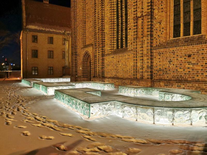 Nocna iluminacja zarysu palatium Mieszka I. Barwa światła w rzeczywistości jest nieco cieplejsza